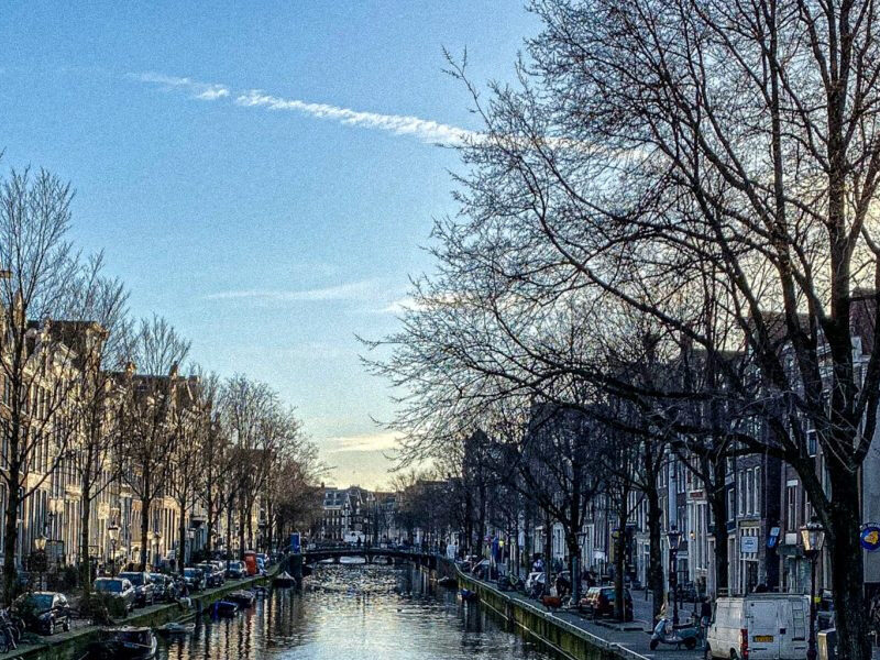 Photo of one of Amsterdams canals with a blue sky.